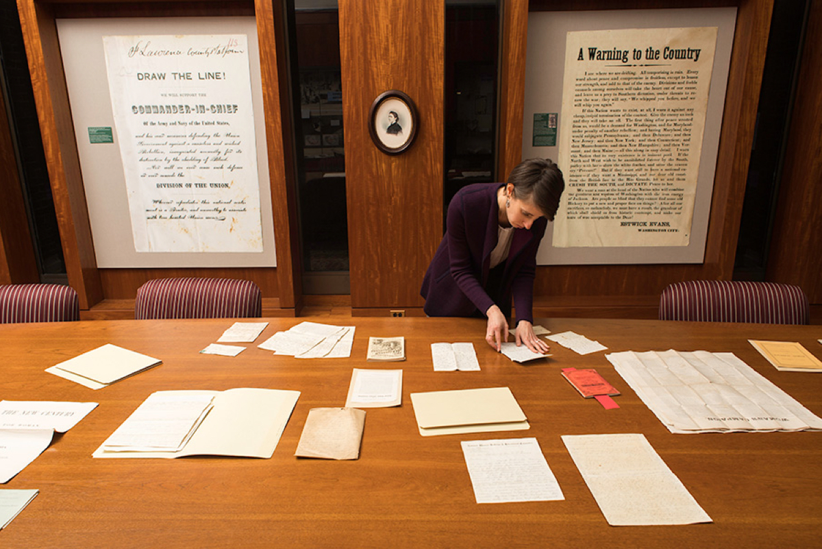 librarian at a large table arranges letters in front of posters about women's suffrage.