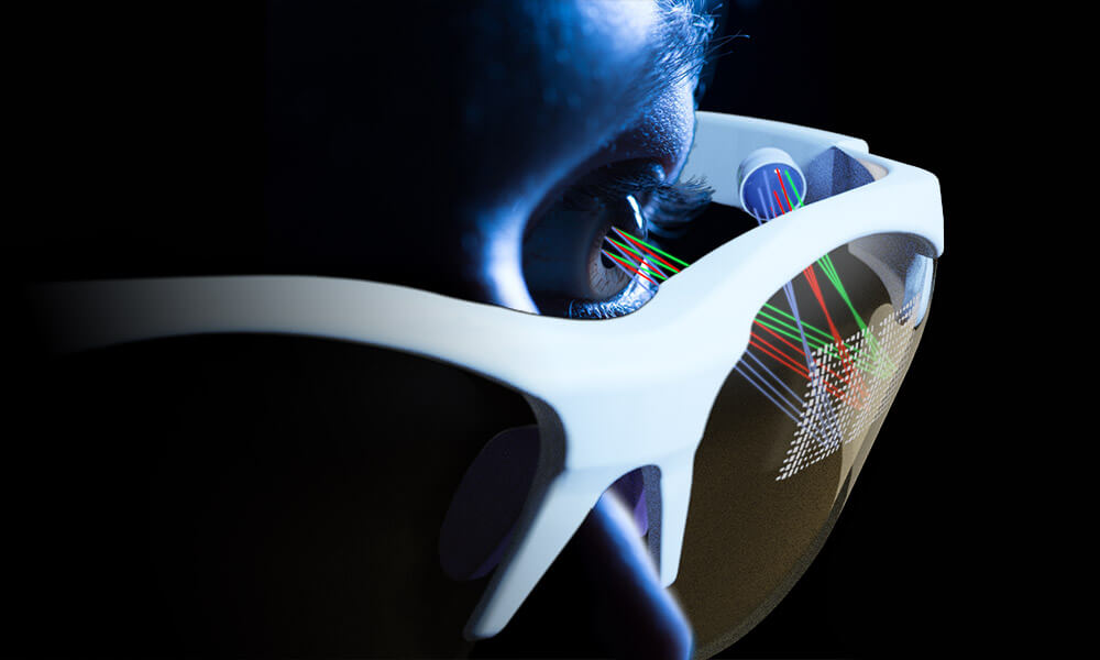 Artist's conception shows a close-up of a face wearing glasses with a square grid of different colored rays being projected on the inside of one of the glasses lenses.