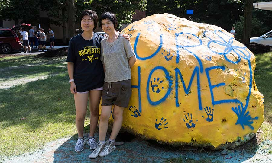mother and daughter standing outside of residence hall in front of a large rock painted to read UR HOME