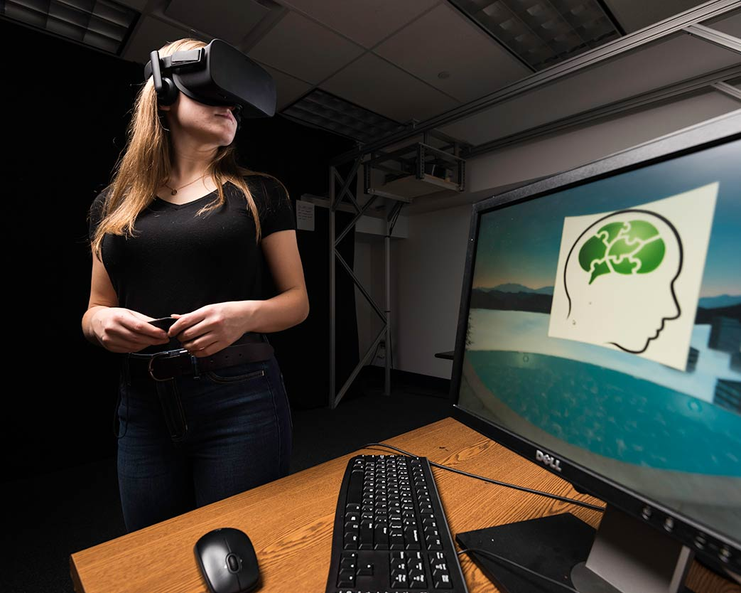 Student stands, wearing virtual reality glasses