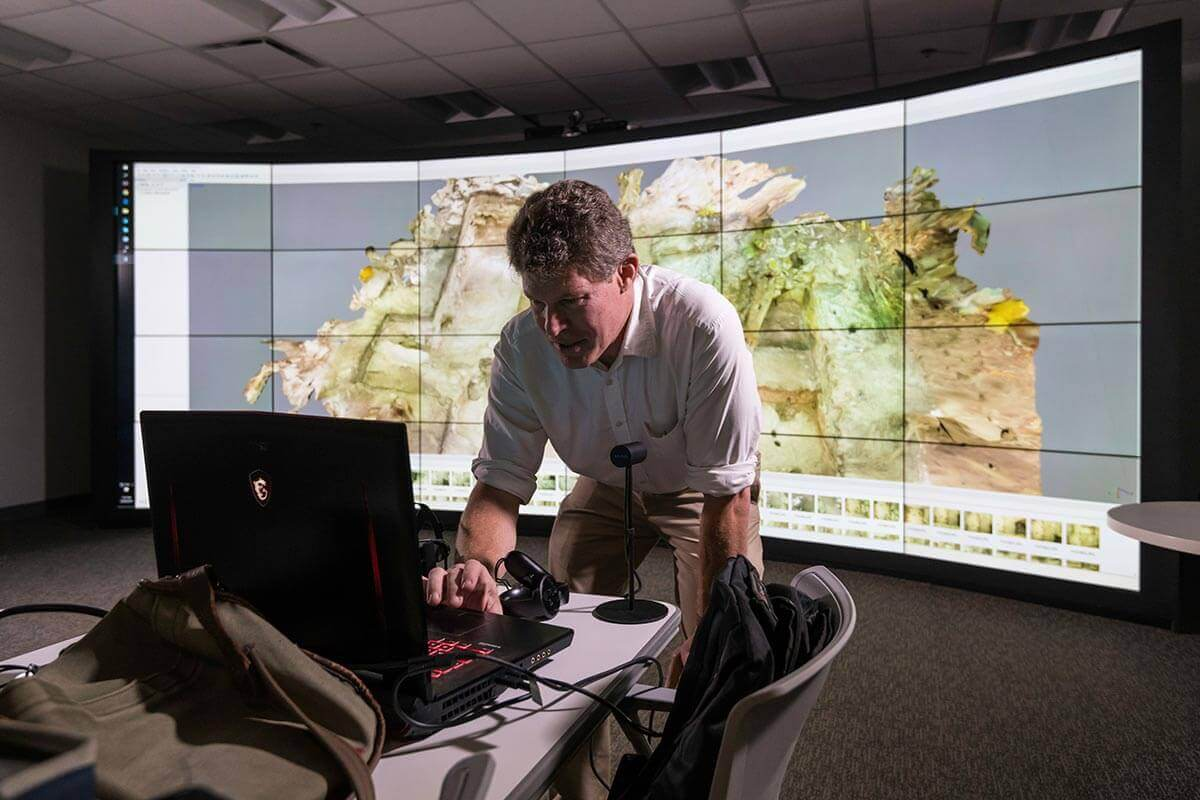 Man leaning over laptop with curved wall monitor display in background at University of Rochester