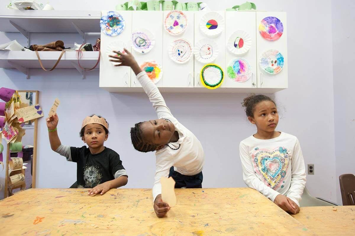 Elementary students at desks raising hands at University of Rochester Mt. Hope Family Center