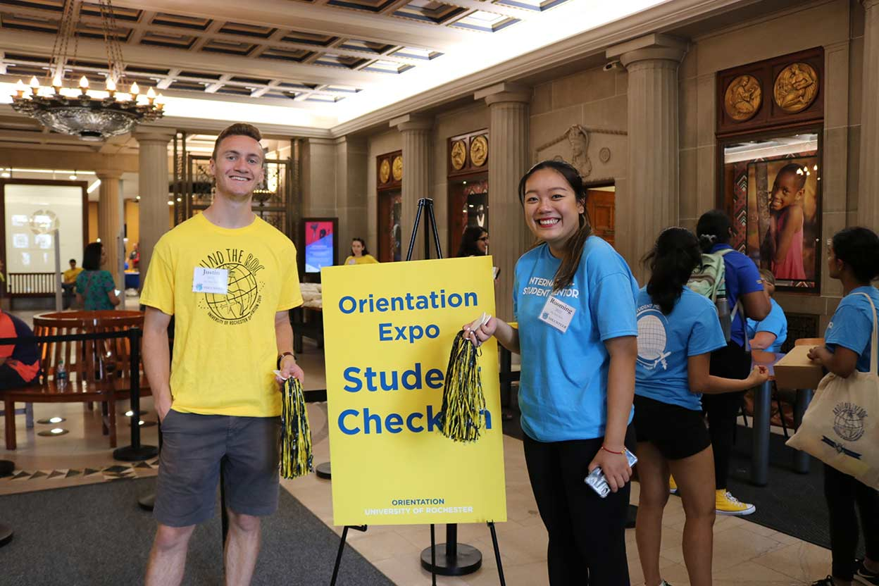 two students smile and stand before a sign that reads ORIENTATION CHECK-IN