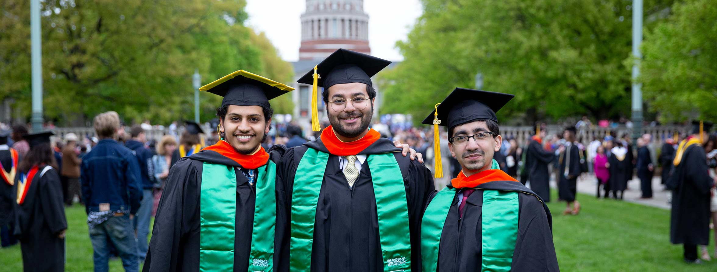 Three students take a picture in cap and gowns during commencement