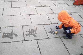 A child writing characters on a sidewalk.