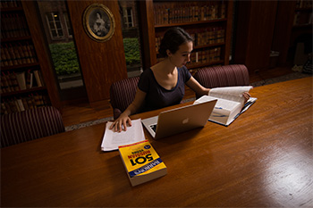 A student works in the Seward Room of Rush Rhees Library.