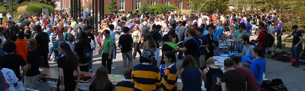 Crowd of students walking between tables on the Wilson Quad