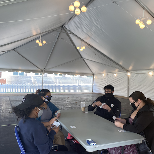 Students sitting at a card table in a tent