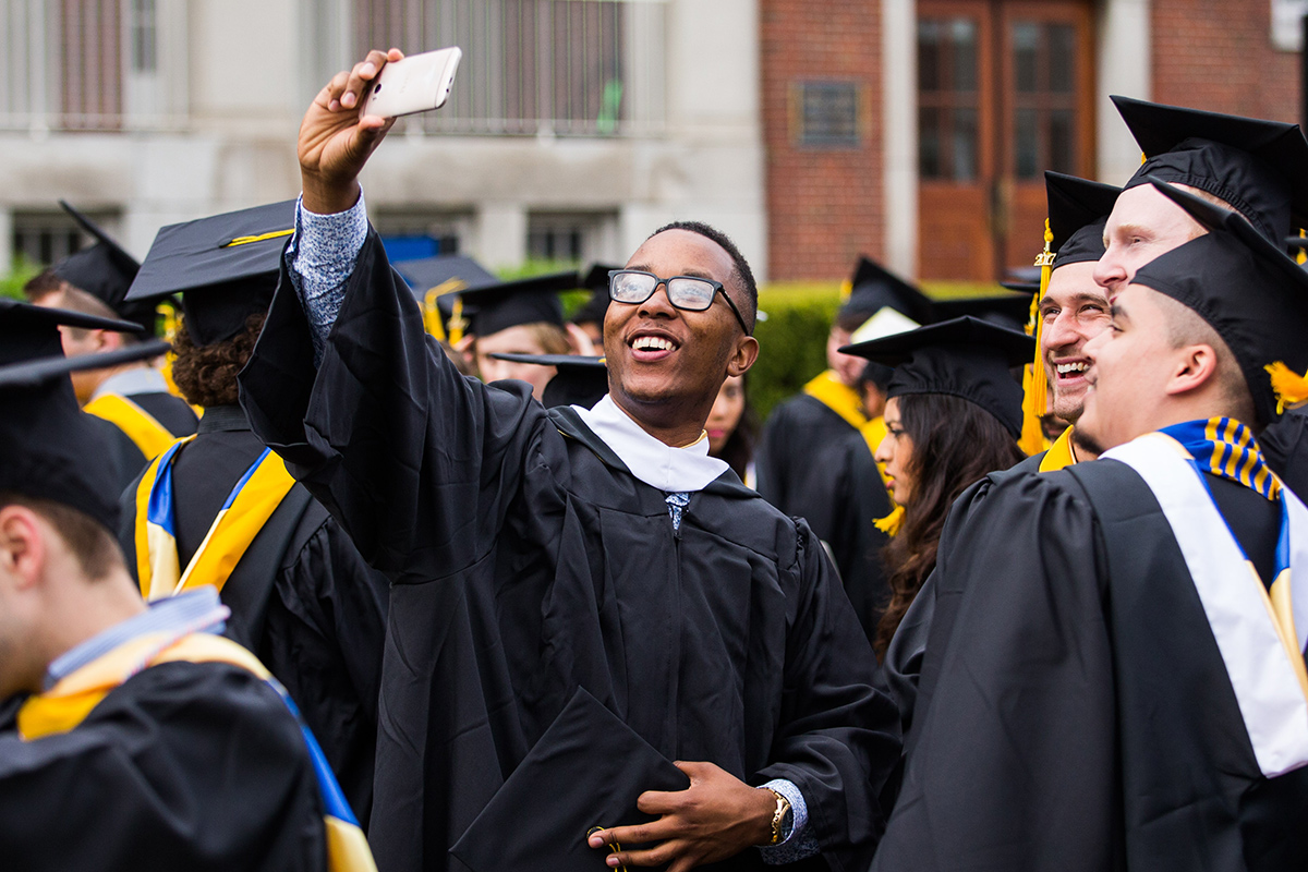 student taking a selfie in a crowd of graduates