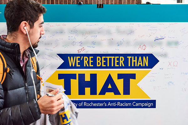student walks past a sign that reads WE'RE BETTER THAN THAT