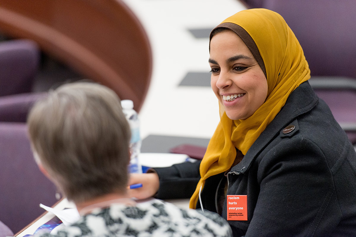 Woman wearing hijab and a button that reads RACISM HURTS EVERYONE speaks to another woman at a conference