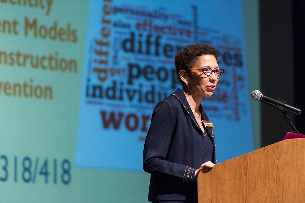 woman speaking at podium with word cloud behind her with phrases like PEOPLE WORLD INDIVIDUAL