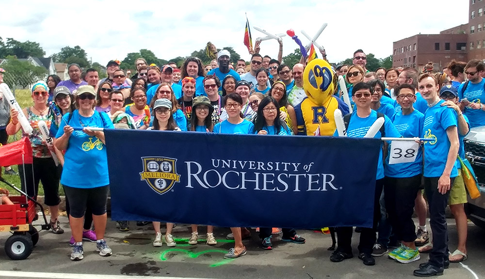 large group pf people and the Rocky yellowjacket mascot march in Pride Parade behind banner reading UNIVERSITY OF ROCHESTER