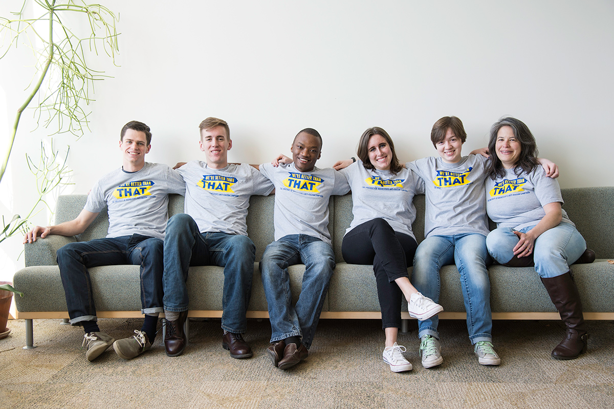 six people sitting on a couch wearing matching t-shirts that read WE'RE BETTER THAN THAT