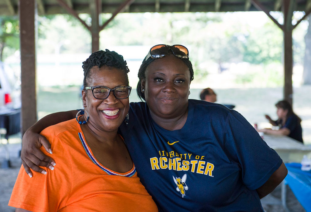 two women, one in University of Rochester t-shirt, smiling and hugging
