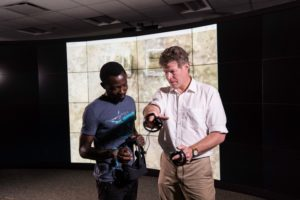 Sebastian Abelezele (ME '20), left uses a virtual reality headset during a meeting of University of Rochester Associate Professor History Michael J. Jarvis' Elmina digital archaeology workgroup as they brainstorm ways to use a digital model they made of Elmina Castle in Ghana this past summer in their research at the VISTA Collaboratory in Carlson Library September 24, 2018. Photo by J. Adam Fenster / University of Rochester
