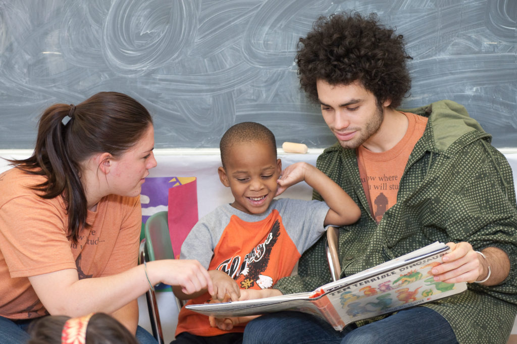Two University of Rochester students reading a picture book to a young child in a children's classroom