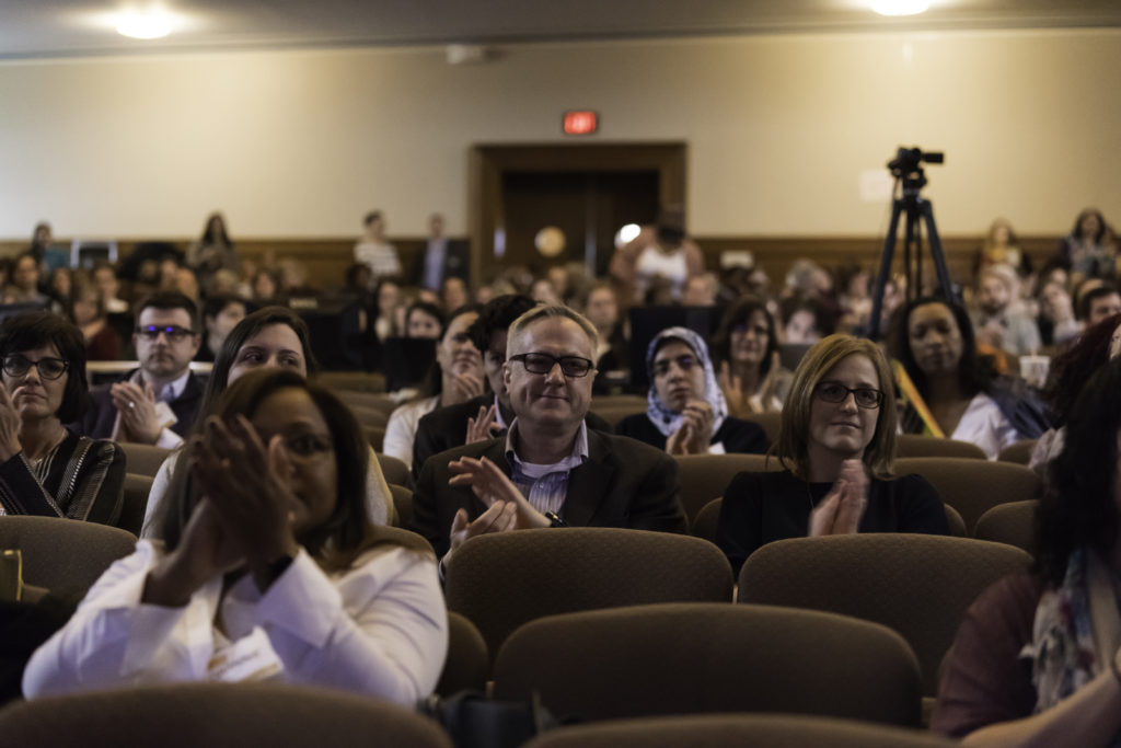 A crowd in seats of an auditorium clapping