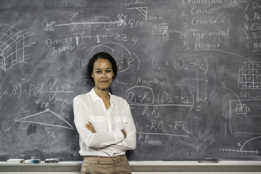 University of Rochester professor in front of her work on a chalkboard
