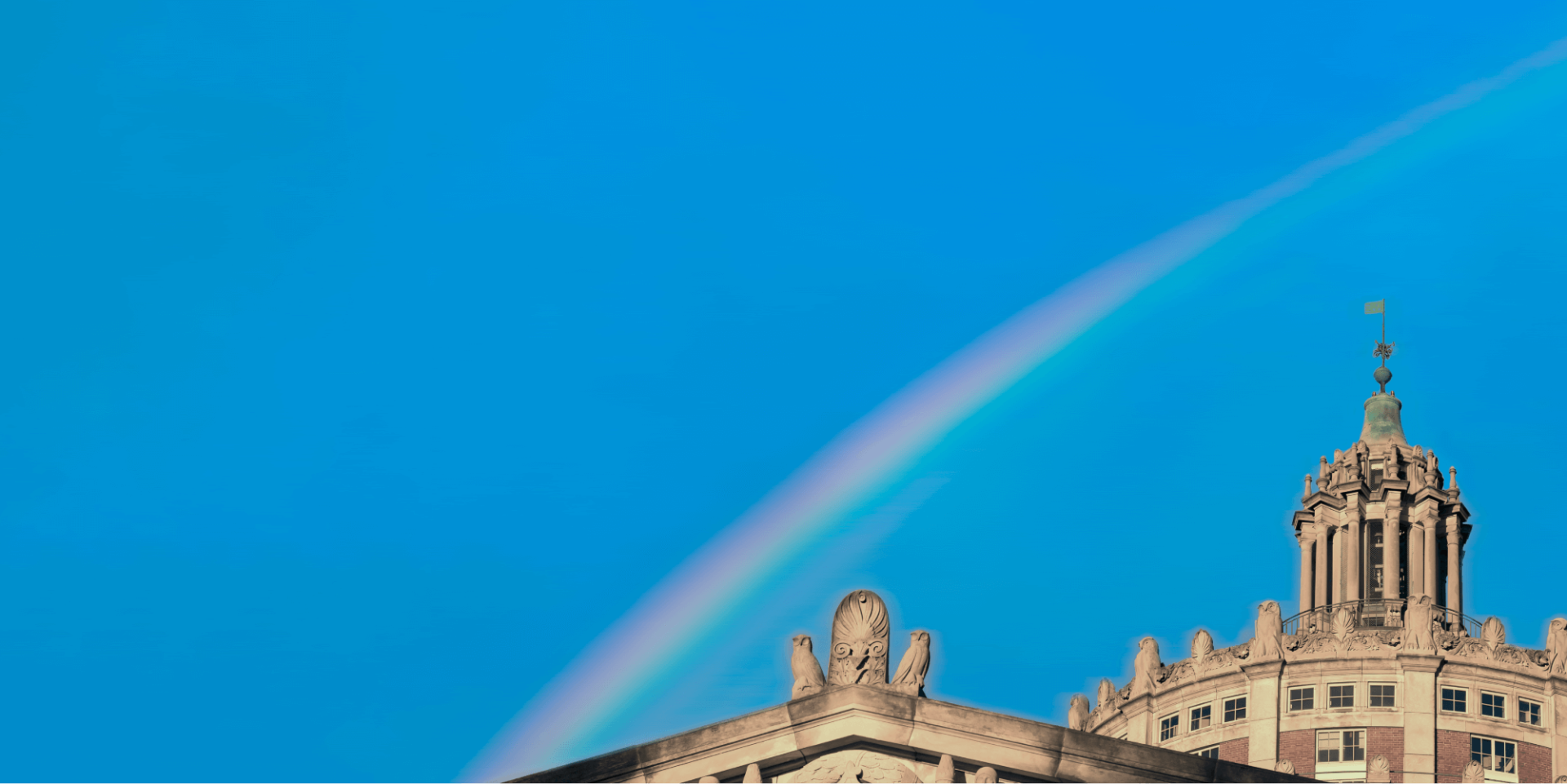 Rush Rhees tower with a blue sky and rainbow