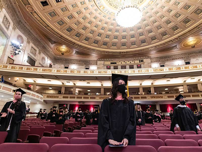several students in cap and gown standing in the seats of the eastman theatre