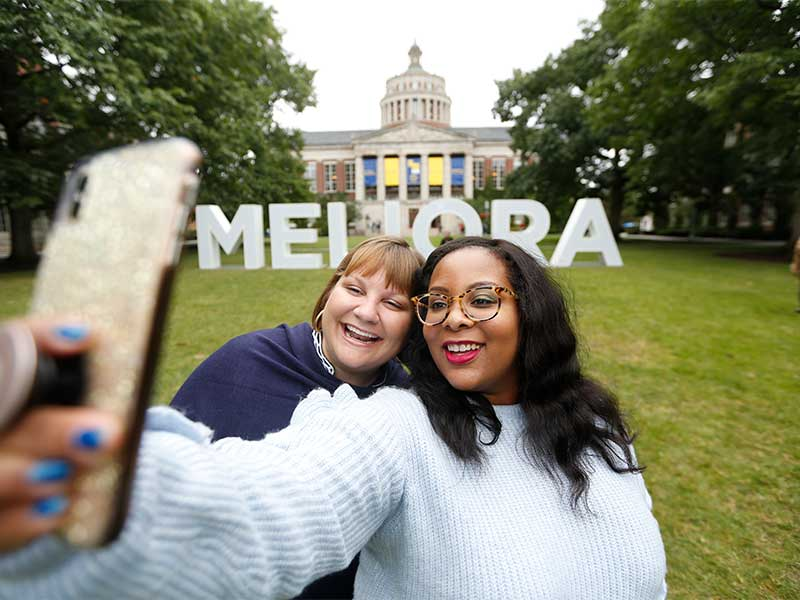 two women taking a selfie in the quad in front of the giant MELIORA letters