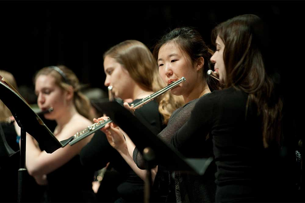 row of flute players in the middle of a performance