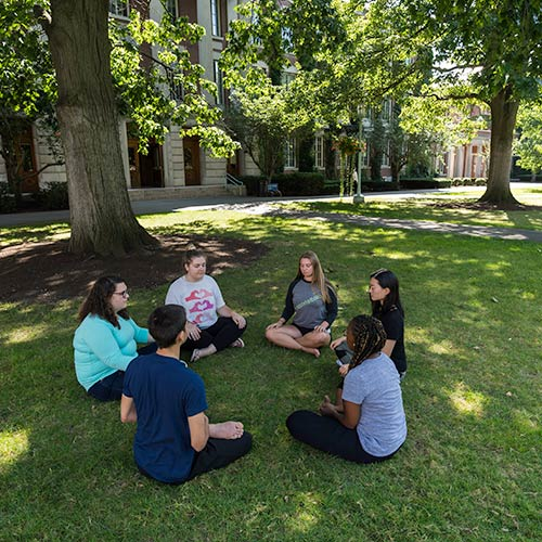 group of students medititating in a circle under a tree.