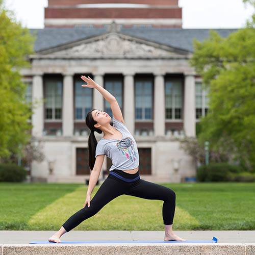 student doing a yoga pose in front of the library building.