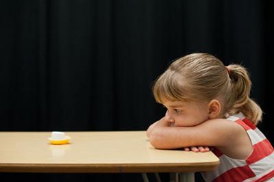 little girl staring at marshmallow