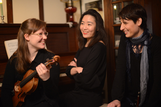 three women, one holding a violin