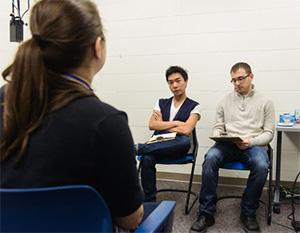 two dour guys taking notes as girl speaks