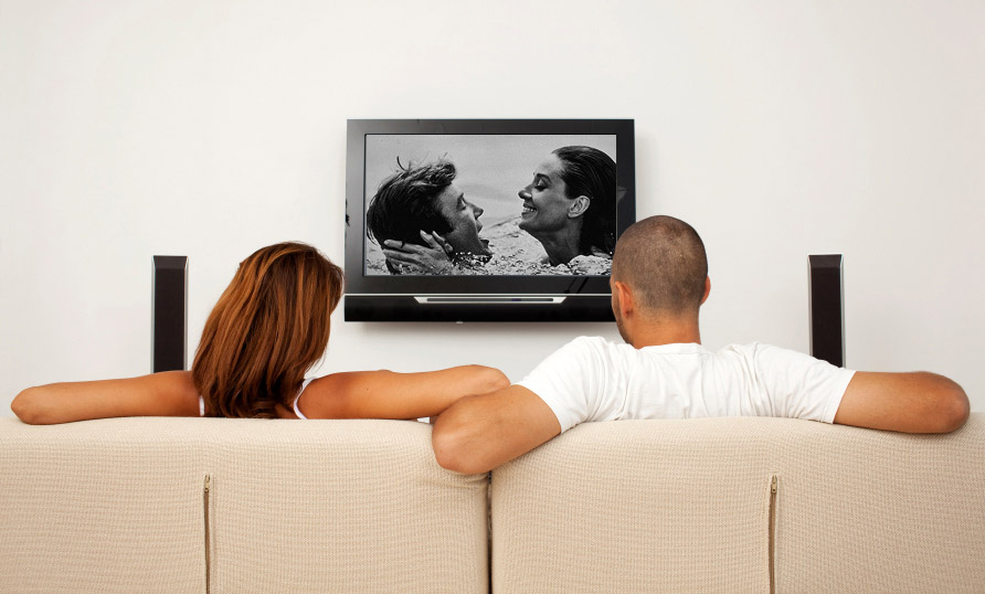 woman and man sit on couch watching a movie.