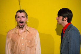 Two actors in front of a yellow backdrop being splashed with water.