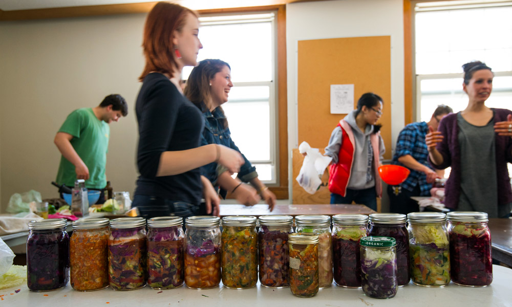 students standing behind a table full of jars of kimchi