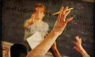 teacher in front of class with students hands raised