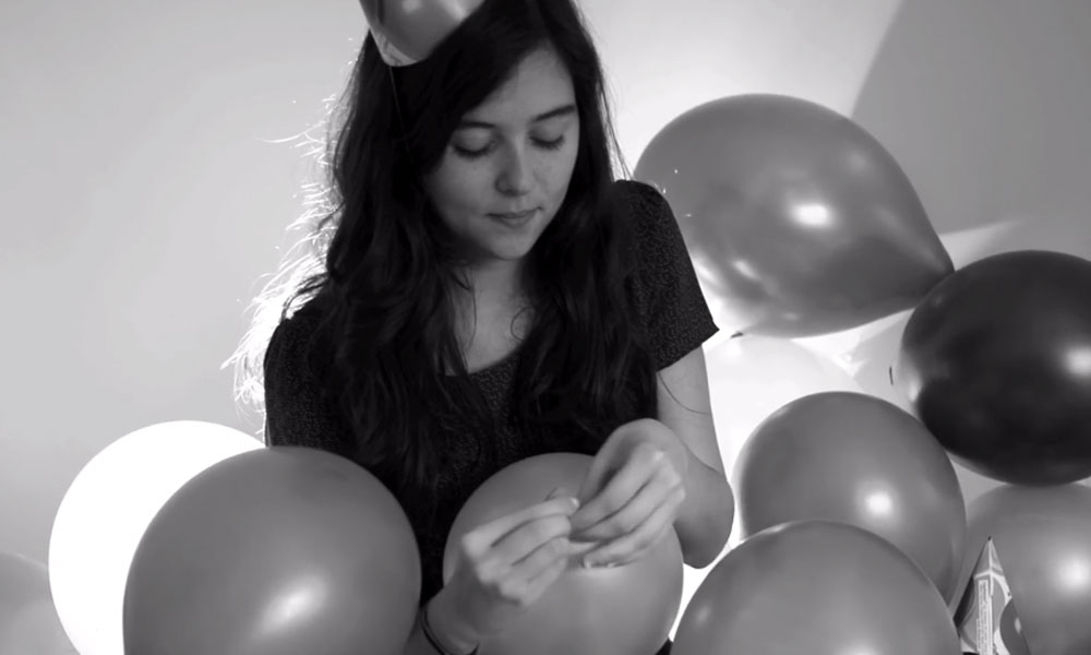 still image from a black-and-white film showing girl blowing up balloons