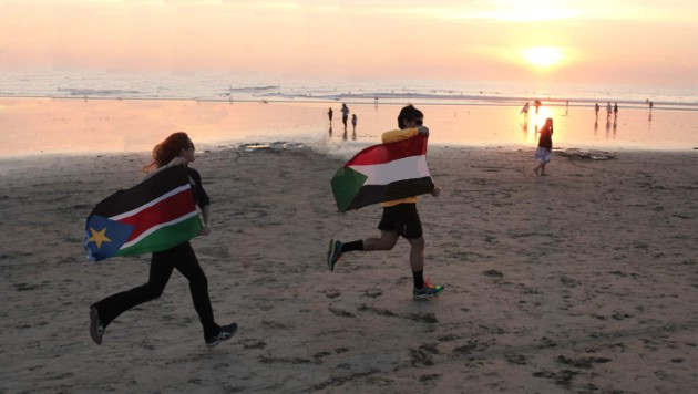 people carrying flags, running on a beach