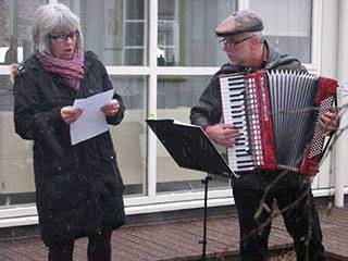 man playing accordian outside next to woman reading