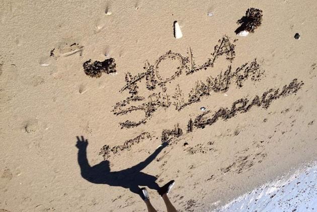 'Hola Sre Lanka from Nicaragua' written in beach sand