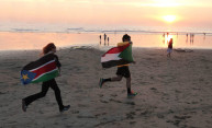 two people running across a beach with the flags of Sudan and South Sudan