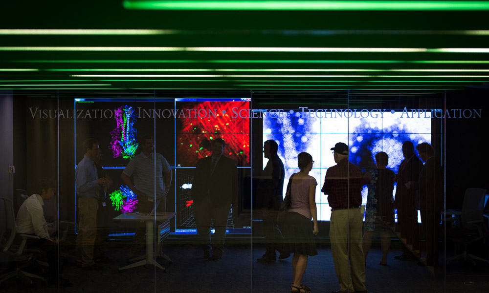 people looking at large wall of colorful computer displays