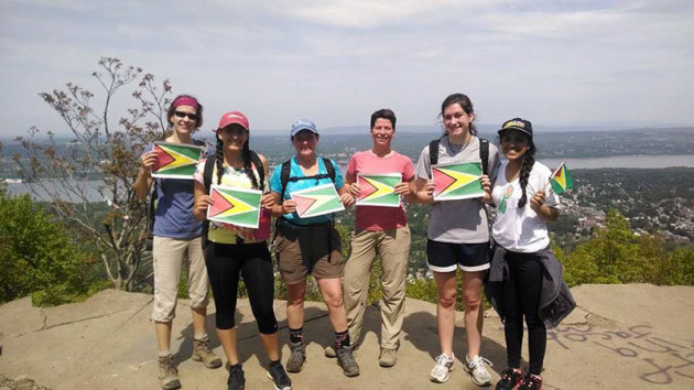 women on a mountain top, holding Guyana's flag