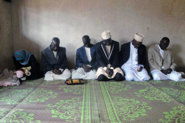 men (and one woman) kneeling in prayer