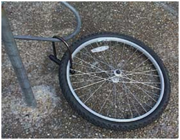 photo of a bike tire locked to a bike rack, after the rest of the bike had been separated from the tire and stolen