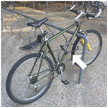 picture of a bike locked to a bike rack, with an arrow pointing to the bike frame where the lock should be placed.