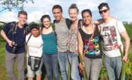 students pose for a photo with community workers in Peru