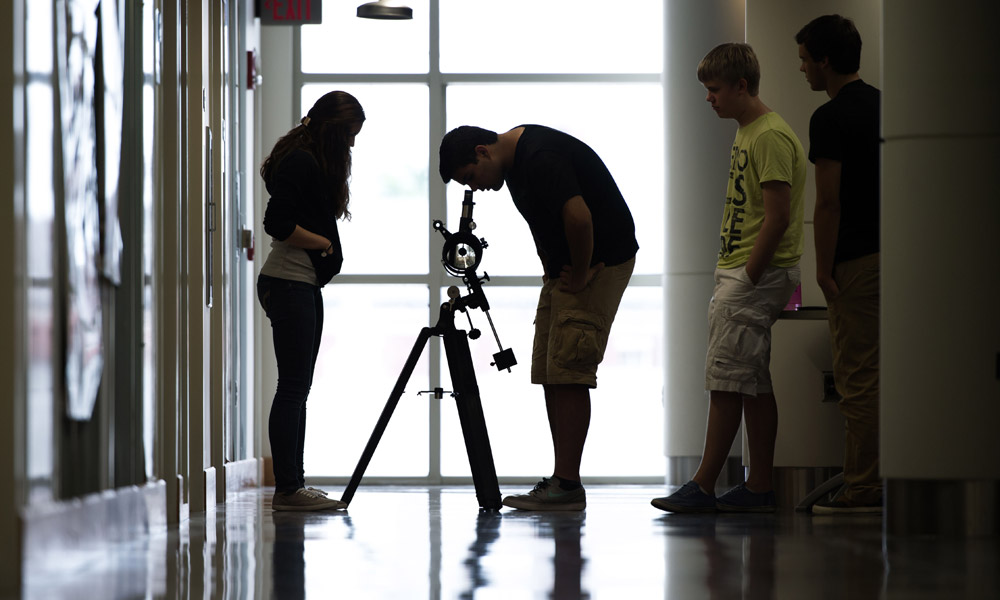 students in a backlit hallway, one of them looking into a telescope