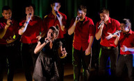 six men and one woman, singing