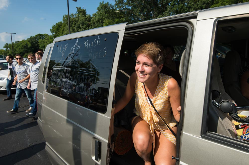 students gets out of a car, windows are decorated with drawings of Rush Rhees Library